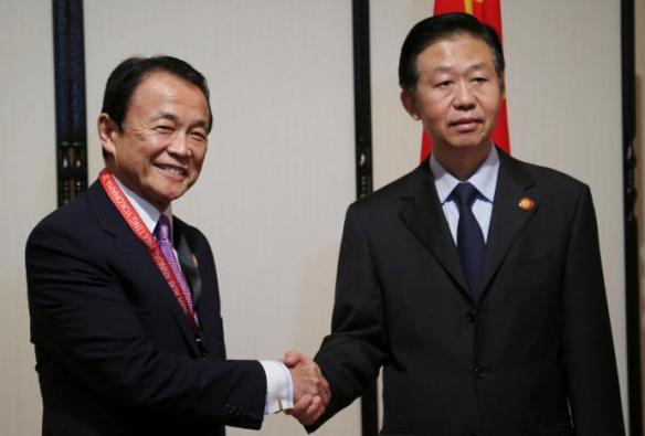 Chinese Finance Minister Xiao Jie (R) and Japanese Finance Minister Taro Aso shake hands in Yokohama