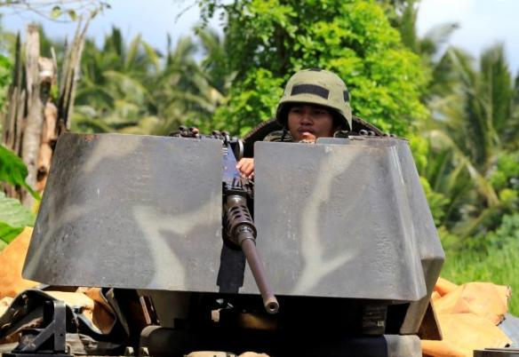 A government soldier atop an armoured personnel carrier is posted along a main highway in Pantar town, Lanao del Norte, after residents started to evacuate their hometown of Marawi